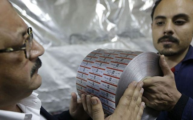 Adel Abd ElSadk, left, examines a final product, aluminum foil printed with the drug name and brand, at his factory financed partly from the Social Development Fund outside Cairo, Egypt. Monday, March 3, 2014 (Photo credit: Amr Nabil/AP)