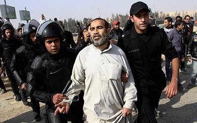 Illustrative: In this Wednesday, January 8, 2014 file photo, Egypt's riot police officers arrest a man, center, following clashes between supporters of Egypt's ousted president Mohammed Morsi and riot police in Cairo, Egypt. (photo credit: AP Photo/Ahmed Gomaa, File)