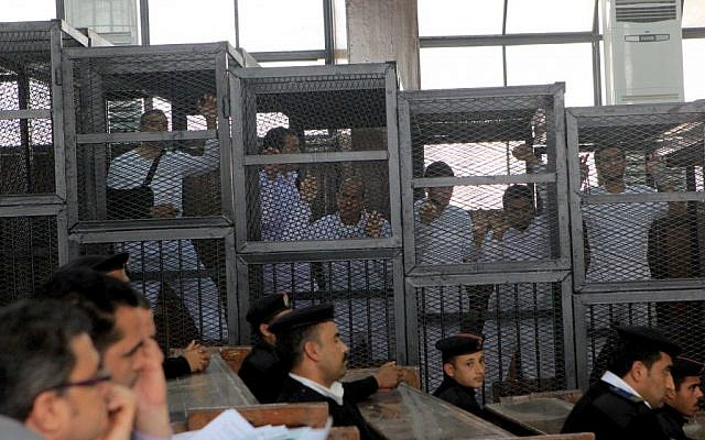Al Jazeera journalists inside the defendants' cage in a courtroom during their trial on terror charges, along with several other defendants, in Cairo Egypt, Wednesday, March 5, 2014. (photo credit: AP/Mohammed Abu Zaid)