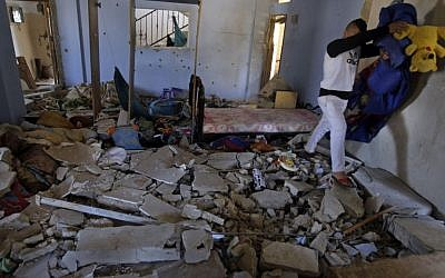 Personal belongings are removed from inside the home of Hamza Abu el-Hija, where he was killed by Israeli troops, in the West Bank refugee camp of Jenin, Saturday, March 22, 2014. (photo credit: AP Photo/Mohammed Ballas)
