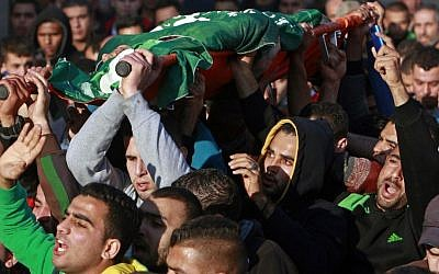 Palestinians carry the body of Hamza Abu al-Hija, who was killed in a raid by Israeli troops, during his funeral procession, in the West Bank refugee camp of Jenin, Saturday, March 22, 2014. (photo credit: AP Photo/Mohammed Ballas)