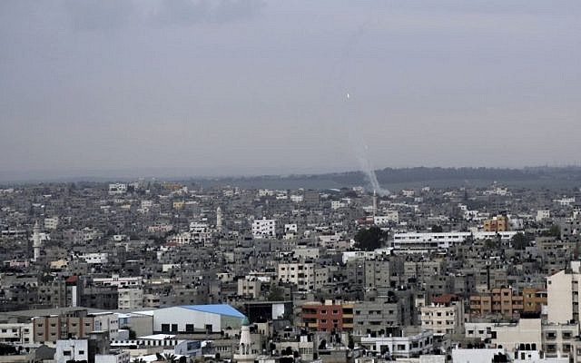 A trail of smoke from rockets fired by Palestinians from Gaza toward Israel is seen above Gaza City on Wednesday, March 12, 2014 (photo credit: AP/Adel Hana)