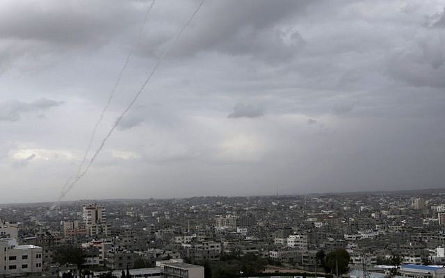 A trail of smoke is seen above Gaza City from rockets fired by Palestinians toward Israel, March 12, 2014 (photo credit: AP/Adel Hana)