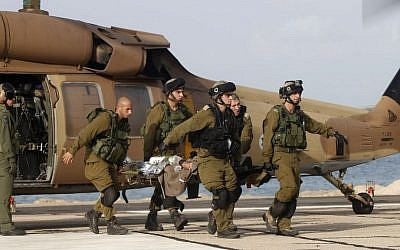 An Israeli soldier injured in a roadside bombing is brought to Rambam Hospital in Haifa on Tuesday (photo credit: AP/
