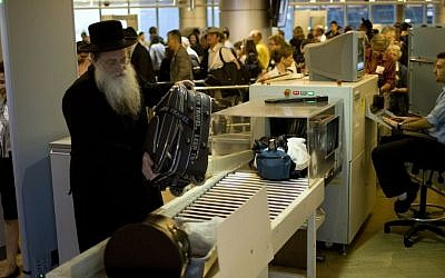 illustrative: Passengers have their hand luggage screened by security personnel at Ben-Gurion Airport, file photo (Ariel Schalit/AP)