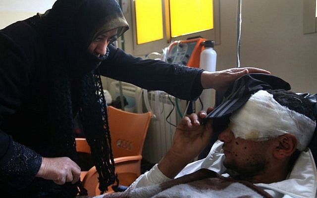Ibrahim, 18, a Syrian rebel who lost one of his eyes during a battle against government forces and Hezbollah fighters in Rima village near Yabroud, lies on his bed as his aunt helps him to put hat on his head, at a makeshift hospital in the Lebanese-Syrian border town of Arsal, eastern Lebanon on Wdnesday, March 5, 2014.  (photo credit: AP/Hussein Malla)