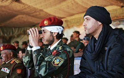 Al-Saadi Gaddafi, in uniform, and his brother Hannibal Gaddafi, right, watch a military exercise in an undated photo released in 2011. (photo credit: AP/Abdel Magid al-Fergany)