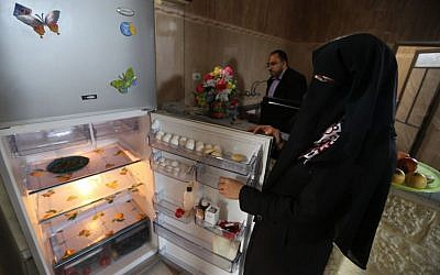 Ahmed Zeitouniya, 32, an employee of the Culture Ministry, helps his wife Minatullah, 29, prepare food in the kitchen of their house in Gaza City in the northern Gaza Strip. Their fridge has been rather empty since Ahmed has not received his salary for the month.(photo credit: AP Photo/Hatem Moussa)