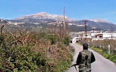 A Syrian fighter holding his weapon after seizing the predominantly Armenian Christian town of Kassab, Syria, March 23, 2014 . (photo credit: AP/Shaam News Network via AP video)