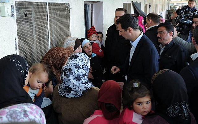 Syrian President Bashar Assad (center right), visits a shelter of internally displaced people in the Damascus suburb of Adra, Syria, on Wednesday, March 12, 2014. (photo credit: AP)