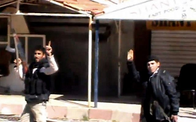 An image taken from video shows Syrian fighters holding their weapons as they gesture after seizing the predominantly Armenian Christian town of Kassab, Syria, March 23, 2014. (AP Photo/Shaam News Network via AP video)