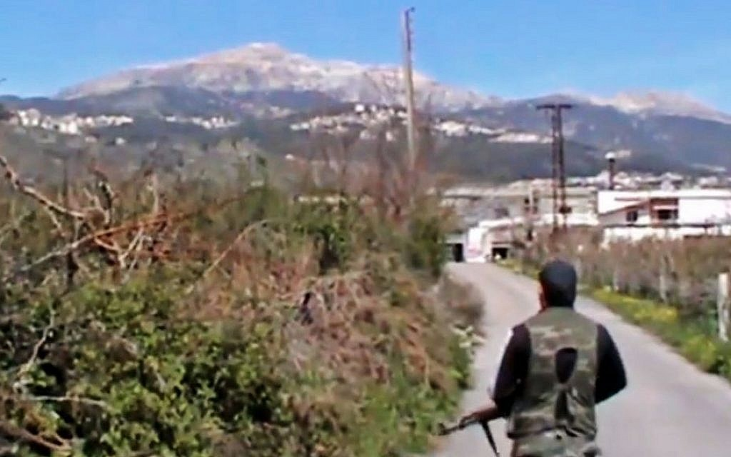 A Syrian fighter holds his weapon after seizing the predominantly Armenian Christian town of Kassab, Syria, near the Turkish border, on March 23, 2014. (AP Photo/Shaam News Network via AP video)