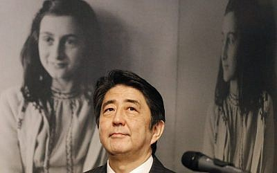 Japan's Prime Minister Shinzo Abe looks at pictures of Anne Frank, rear, as he visits the Anne Frank House museum in Amsterdam, Netherlands, Sunday, March 23, 2014. Abe expressed regrets that 300 copies of Anne Franks' diary were vandalized recently in Tokyo libraries. (photo credit: AP/Frank Augstein)