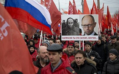 Demonstrators march in support of Kremlin-backed plans for the Ukrainian province of Crimea to break away and merge with Russia, in Moscow, Saturday, March 15, 2014. A poster depicts photos of a WWII German prisoner of war and Ukrainian Prime Minister Arseniy Atsenyuk, and says 'Your project is doomed, grandson' (AP Photo/Alexander Zemlianichenko)