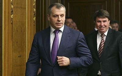 Crimea's prime minister Sergei Aksyonov, center, enters a hall prior to talks in the Russian Parliament in Moscow, Friday, March 7, 2014. (AP Photo/Alexander Shalgin)