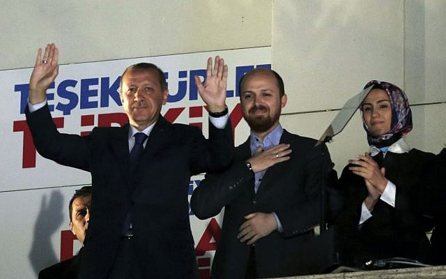 Turkey's Prime Minister Recep Tayyip Erdogan, his son Bilal Erdogan and daughter Sumeyye Erdogan salute supporters from the balcony of his ruling party headquarters in Ankara, Turkey, early Monday, March 31, 2014. (photo credit: AP)