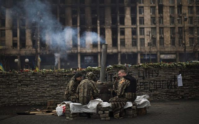 Anti-Yanukovych protesters wearing fatigues guard a barricade in Kiev's Independence Square, the epicenter of the country's current unrest, Ukraine, on Saturday, March 1, 2014. (photo credit: AP Photo/Emilio Morenatti)