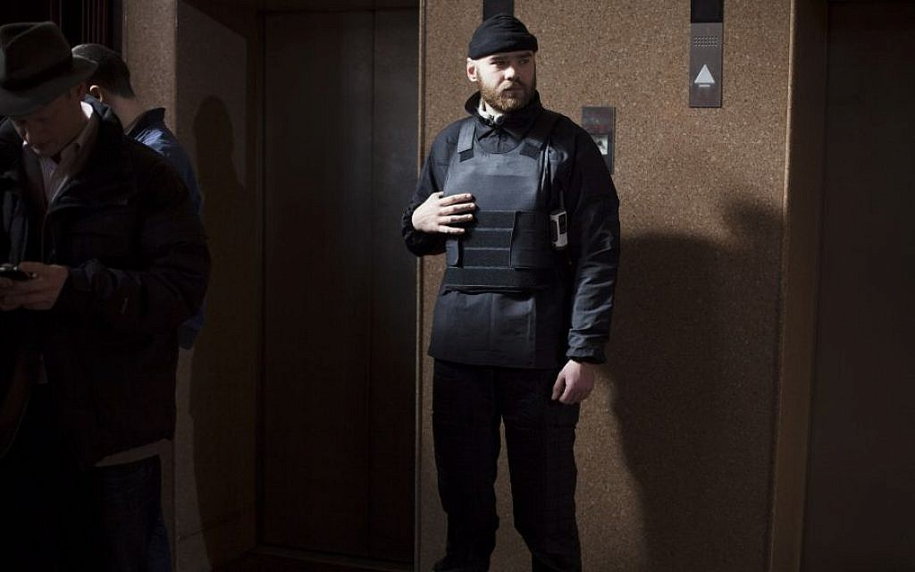 A Right Sector member stands guard next to elevators on the ground floor of the Dnipro hotel near Independence Square, Kiev, Ukraine, on March 7, 2014 (photo credit: AP/David Azia)