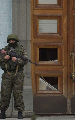An unidentified man guards the entrance to a local government building in Simferopol, Ukraine, on Saturday, March 1, 2014. (AP Photo/Ivan Sekretarev)