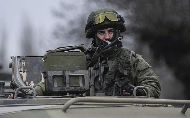 A man in unmarked uniform looks from atop of a military vehicle while standing guard as troops taking control the the Coast Guard offices in Balaklava, outskirts of Sevastopol, Ukraine, Saturday, March 1, 2014 (photo credit: AP/Andrew Lubimov)
