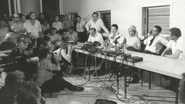 Uri Bar-Lev (with tie) and colleagues speak to the media on their safe return to Israel (photo credit: Courtesy El Al archive)