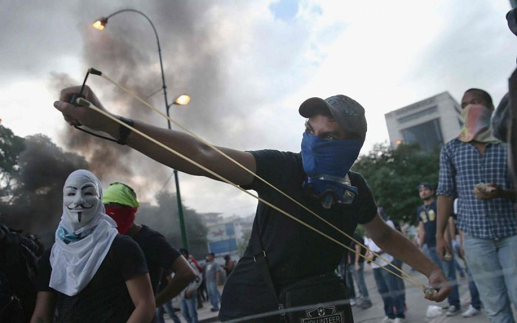 A man shoots a slingshot at national guard troops following one of the largest anti-government demonstrations yet on March 2, 2014 in Caracas, Venezuela. (John Moore/Getty Images/JTA)