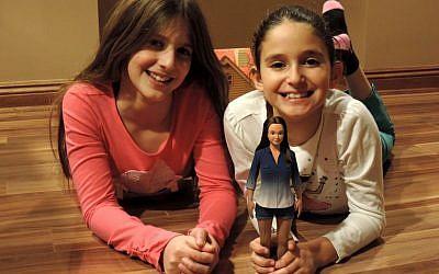 Nickolay Lamm's cousins play with a prototype of the Lammily doll. (photo credit: JTA, courtesy of Nickolay Lamm)