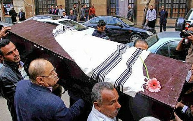 Egyptians carry the coffin of Nadia Haroun, the deputy head of the dwindling Jewish community, outside the Jewish synagogue, Shaar Hashamayim in Cairo, Egypt, Tuesday, March 11, 2014 (photo credit: AP/Ahmed Gomaa)