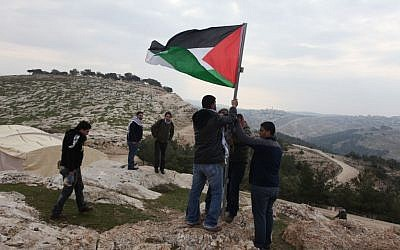 Palestinian activists place a flag post in E1 east of Jerusalem, lying within area C of the West Bank (photo credit: Issam Rimawi/Flash90)