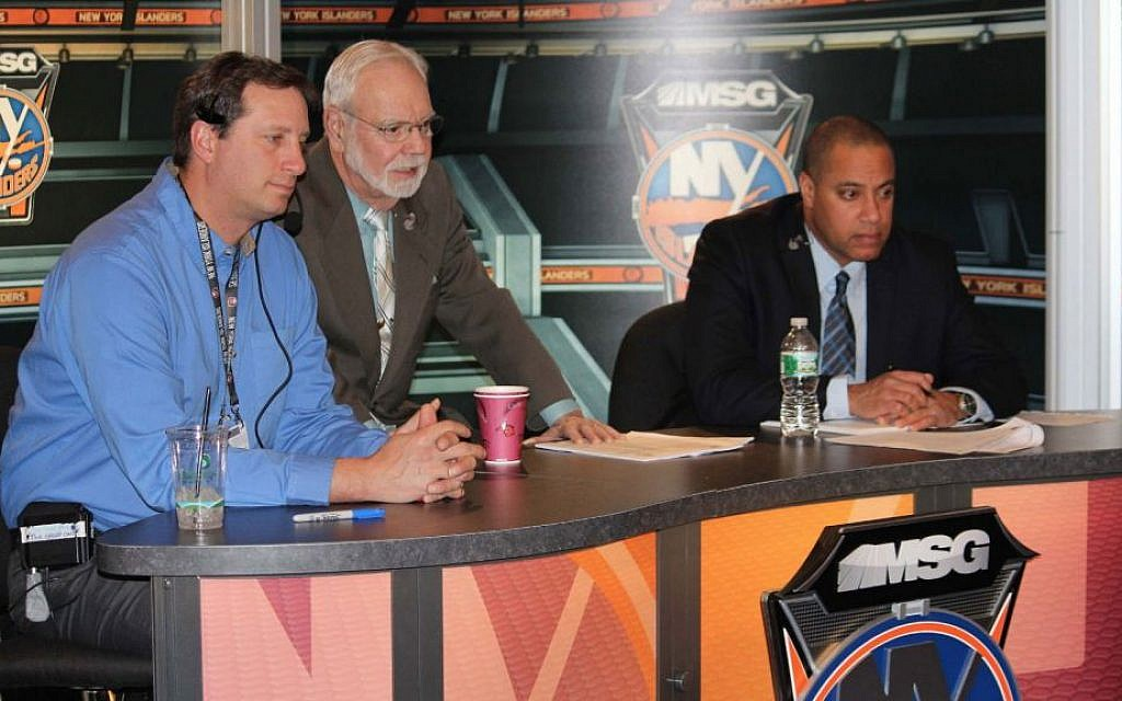 Stan Fischler is flanked by producer Glenn Petraitis, left, and co-host Peter Ruttgaizer at the Nassau Coliseum set of their pregame and postgame shows. (Hillel Kuttler/JTA)