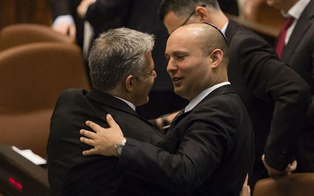 Jewish Home's Naftali Bennett seen with Yesh Atid's Yair Lapid, after the Draft law passed unanimously in the Knesset, March 12, 2014. (Flash90)
