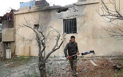 A Lebanese man holds part of an exploded rocket that hit a house in the predominately Shiite town of Labweh, near the border with Syria, northeast Lebanon, Monday March 17, 2014 (photo credit: AP/Hussein Malla)