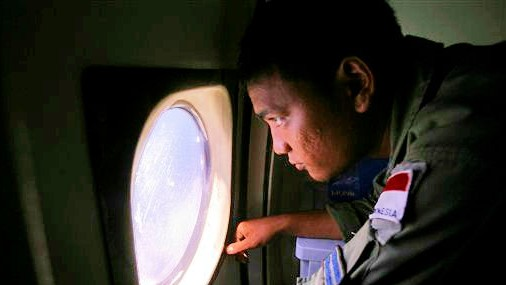 An Indonesian Navy crew member scans the water bordering Indonesia, Malaysia and Thailand during a search operation for the missing Malaysian Airlines Boeing 777 near the Strait of Malacca on Monday, March 10, 2014. (photo credit: AP/Binsar Bakkara)