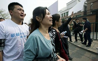 Relatives of Chinese passengers onboard Malaysia Airlines Flight 370 cry as they protest outside the Malaysian Embassy in Beijing, China, Tuesday, March 25, 2014. (photo credit: AP Photo/Ng Han Guan)