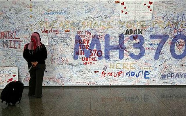 A woman reads messages for passengers aboard a missing Malaysia Airlines plane, at Kuala Lumpur International Airport in Sepang, Malaysia, Tuesday, March 18, 2014 (photo credit: AP /Lai Seng Sin)