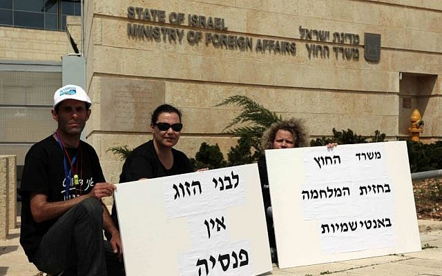 Striking workers outside the Foreign Ministry in Jerusalem, on Monday, March 24, 2014. Signs read: 'The couple has no pension' and 'The Foreign Ministry is on the front lines against anti-Semitism' (photo credit: Meital Cohen/Flash90)