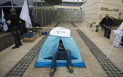 A Foreign Ministry worker lying in a tent as he strike outside the Foreign Ministry offices in Jerusalem, on March 24, 2014. (photo Yonatan Sindel/Flash90)