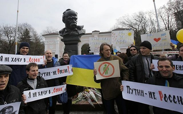 People shout slogans as they stand next to a statue of Ukrainian poet Taras Shevchenko, during a rally against the breakup of the country in Simferopol, Crimea, Ukraine, Thursday, March 9, 2014. (photo credit: AP Photo/Darko Vojinovic)