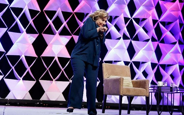 Hillary Clinton ducks after a woman threw an object toward her while she was delivering remarks at the Institute of Scrap Recycling Industries conference on April 10, 2014 in Las Vegas, Nevada. (photo credit: Isaac Brekken/Getty Images/AFP)