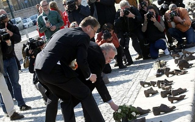 Hungarian politicians light candles at the Holocaust memorial on the Danube river bank in Budapest on April 16, 2014 (photo credit: AFP/ Ferenc Isza)
