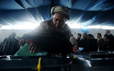An Afghan man casts his vote at a local polling station in Kabul on Saturday, April 5, 2014 (photo credit: AFP/Shah Marai)