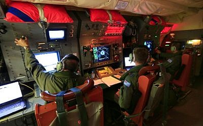 Australian Defence handout photo taken on April 1, 2014, and released on April 3, shows crew members on board an RAAF Orion during the search for missing Malaysia Airlines Flight MH370 in the southern Indian Ocean. (photo credit: AFP/Australian Defence/Cpl David Gibbs)