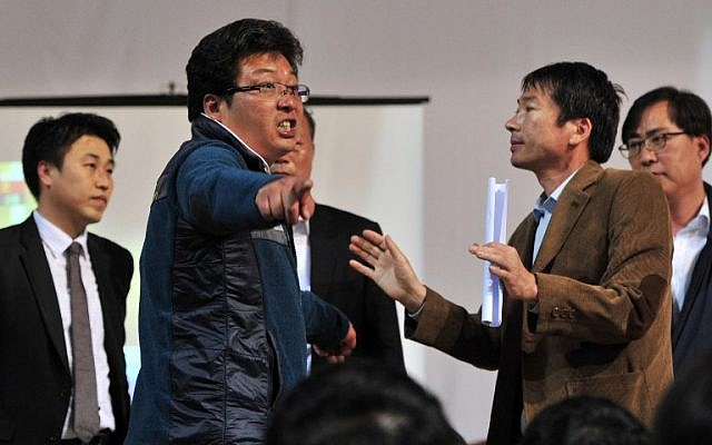 A relative (2nd L) of a passenger on board a capsized ferry argues with South Korean government officials as the officials try to brief them on the rescue situation, at a gym in Jindo on April 17, 2014.  (photo credit: AFP/ JUNG YEON-JE)
