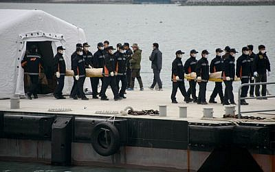 """The bodies of victims recovered from the """"Sewol"""" ferry are carried to waiting ambulances at Jindo harbor on April 22, 2014. (photo credit: AFP Photo/Ed Jones)"""