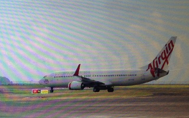 This photo taken through the window of a plane shows a Virgin Australia plane at the center of a hijacking scare sitting on the tarmac at Bali airport in Denpasar on Friday, April 25, 2014 (photo credit: AFP)