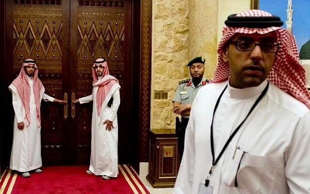 Aides to Saudi King Abdullah stand outside a room in the monarch's desert camp about 60 kilometers northeast of Riyadh while he meets with US President Barack Obama, March 2014. (photo credit: Saul Loeb/AFP)