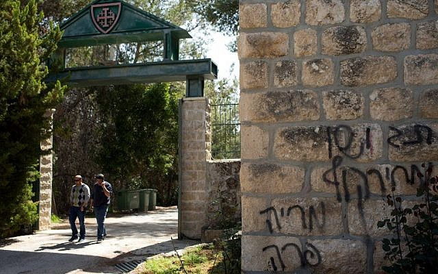 People leave the Deir Rafat Catholic convent whose walls can be seen sprayed with graffiti reading 'Jesus is a monkey,' Mary is a cow,' and 'price tag,' Tuesday, April 1, 2014, near the Israeli city of Beit Shemesh (photo credit: AFP/Menahem Kahana)