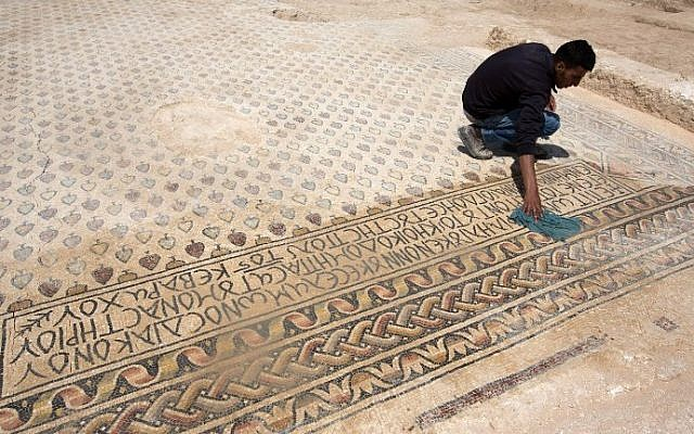 An archaeologist cleans a Byzantine mosaic floor that decorated a monastery during infrastructure work in the Bedouin village of Hura in the Northern part of the Negev desert, Tuesday, April 1, 2014. (photo credit: Menahem Kahana/AFP)