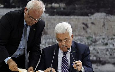 Palestinian Authority President Mahmoud Abbas (R) signs a request to join 15 United Nations-linked and other international treaties at his headquarters in the West Bank city of Ramallah on Tuesday, April 1, 2014 (photo credit: AFP/Abbas Monami)