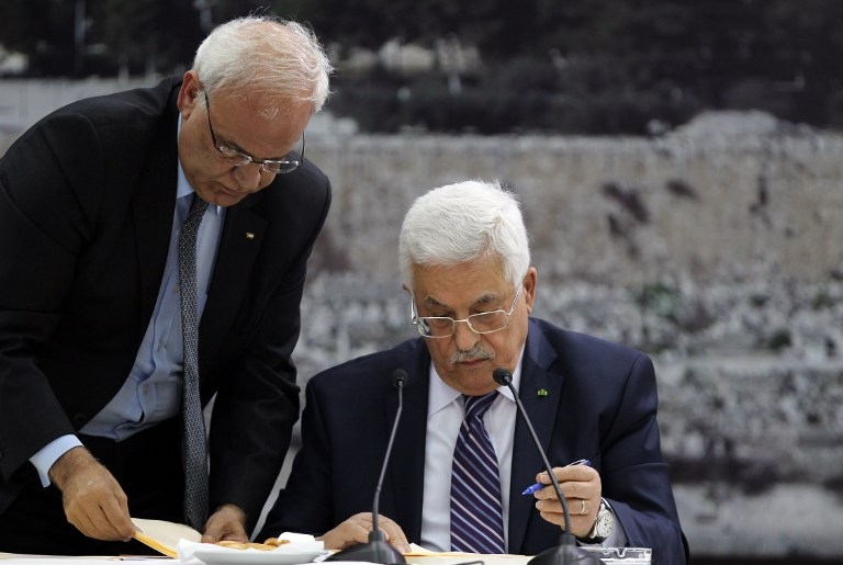Palestinian Authority President Mahmoud Abbas (R) signs a request to join 15 United Nations agencies at his headquarters in the West Bank city of Ramallah on Tuesday, April 1, 2014 (photo credit: AFP/Abbas Monami)